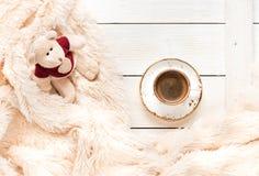 El pequeño oso hecho punto del juguete del bebé se sienta en una manta caliente y una taza de café fotografía de archivo