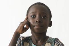 El pequeño pensamiento africano del niño tiene una idea, aislada en blanco Fotos de archivo libres de regalías
