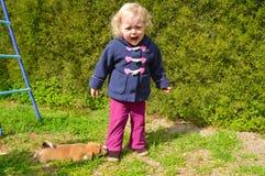 El pequeño perrito está tirando de la pequeña muchacha hermosa por Fotos de archivo libres de regalías