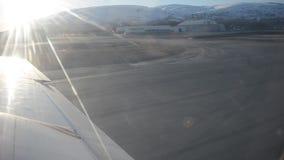 El pequeño tomar del avión de propulsor de la pista del aeropuerto de Tromsoe, langens en sol brillante