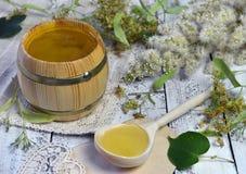 El pequeño tubo de miel, cucharea por completo de las flores de la miel y del tilo en tablones de madera Imagen de archivo libre de regalías