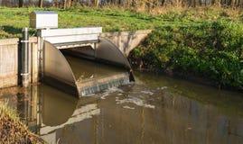 El pequeño vertedero controla el nivel del agua en la corriente Imágenes de archivo libres de regalías