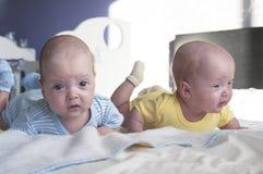 El pequeños muchacho y muchacha lindos de bebés de los gemelos están mintiendo en la cama y están aprendiendo llevar a cabo sus c foto de archivo libre de regalías