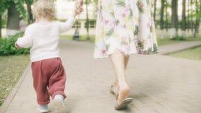 El peque?o beb? camina llevando a cabo la mano de su mam? en el parque en un d?a de verano almacen de video