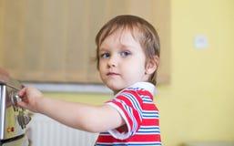 El pequeño bebé es la cocina conmovedora - peligro en hogar Imagen de archivo libre de regalías