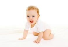 El pequeño bebé sonriente feliz se arrastra en el fondo blanco Imagenes de archivo