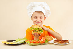 El pequeño cocinero divertido en sombrero de los cocineros goza el cocinar de la hamburguesa sabrosa Foto de archivo