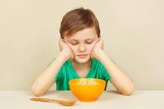 El pequeño muchacho descontentado no quiere comer las gachas de avena Imágenes de archivo libres de regalías