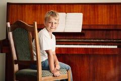 El pequeño muchacho feliz juega el piano Foto de archivo libre de regalías