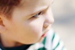 El pequeño muchacho hermoso serio mira la cámara en parque Imagen de archivo