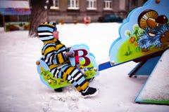 El pequeño niño sacude en el oscilación en el patio en invierno Imagen de archivo