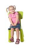 El pequeño niño se sienta en una silla Fotos de archivo