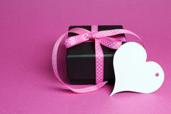 El pequeño regalo especial del presente de la caja negra con la cinta rosada del lunar y el corazón blanco forman la etiqueta del  Foto de archivo