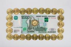 El perímetro alineado milésimo billete de banco del ruso del diez monedas en el medio de la moneda es a imagen de archivo libre de regalías