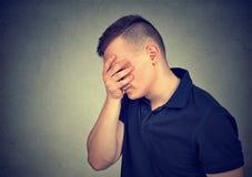 El perfil lateral de un hombre triste con entrega su cara Imagen de archivo