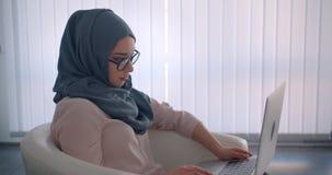 El perfil tirado de empresaria musulm?n en el funcionamiento del hijab y de vidrios con el ordenador port?til atento sonr?e en c? almacen de video