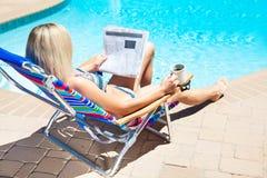 El periódico de la lectura de la mujer cerca de la piscina Imágenes de archivo libres de regalías