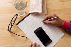El periódico del café de la taza da el teléfono celular fotografía de archivo libre de regalías