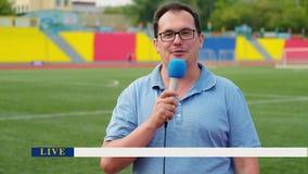 El periodista está divulgando del estadio para la televisión con el panel de las noticias de última hora almacen de metraje de vídeo