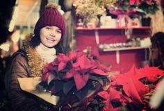 El permanecer adolescente con la composición floral en la Navidad justa Imágenes de archivo libres de regalías