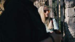 El permanecer que espera de la chica joven sola en la parada de autobús en la chaqueta y las gafas de sol, tráfico almacen de metraje de vídeo