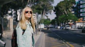 El permanecer que espera de la chica joven sola en la parada de autobús en la chaqueta y las gafas de sol, tráfico almacen de video