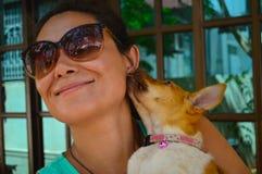 El perrito rojo lame la cara linda de la muchacha fotografía de archivo libre de regalías