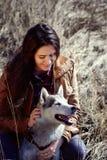 El perro esquimal de la muchacha está rasguñando detrás del oído y sonríe Fotos de archivo libres de regalías