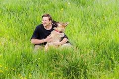 El perro lame su amo un hombre que abraza a un pastor alemán Imagenes de archivo