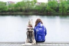 El perro y la mujer se sientan en la orilla del río Imagen de archivo