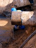 El personal del trabajador cortó el tubo grande del metal con la amoladora Parques rojos ardientes Imagenes de archivo