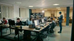 El personal está funcionando en la oficina en los ordenadores en el escritorio común por la tarde almacen de metraje de vídeo
