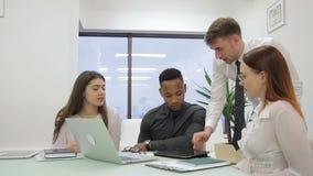 El personal joven comunica en la tabla con el ordenador portátil en compañía principal almacen de metraje de vídeo