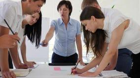 El personal sugiere el desarrollo de negocios de las ideas al lado del escritorio en la sala de conferencias metrajes