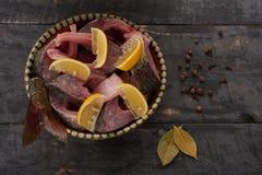 El pescado fresco junta las piezas en un cuenco y un limón Fotografía de archivo