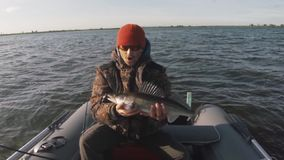 El pescador aficionado besa pescados almacen de metraje de vídeo