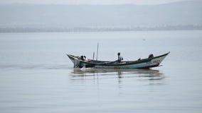 El pescador africano está pasando cerca de la orilla en barco y está remando solamente en el mar almacen de video