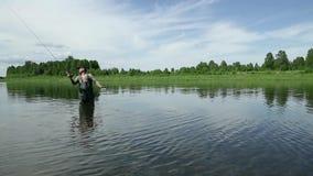 El pescador alegre está pescando en agua de río tranquila cerca de la orilla almacen de metraje de vídeo