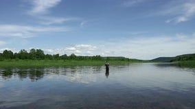 El pescador alegre está pescando en agua de río tranquila cerca de la orilla almacen de video