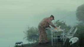 El pescador cambia su cuchara-cebo almacen de video
