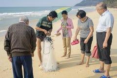El pescador chino muestra la captura en los transeúntes de las redes imagenes de archivo
