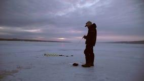 El pescador coge el lucio en la puesta del sol en la oscuridad almacen de metraje de vídeo
