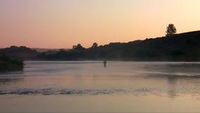 El pescador coge pescados en el amanecer en la niebla almacen de video