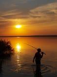 El pescador coge pescados en el lago en la puesta del sol Fotos de archivo