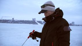El pescador coge pescados en el invierno y mira la mordedura almacen de metraje de vídeo