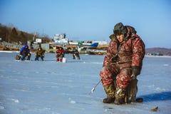 El pescador coge pescados en la isla rusa 22 de Rusia Vladivostok del invierno 12 2013 Fotos de archivo libres de regalías