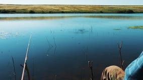 El pescador coge pescados en trole en la orilla del lago Superficie hermosa lisa del agua El pescador está esperando metrajes