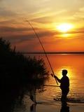 El pescador coge pescados haciendo girar en el lago en la puesta del sol Imagen de archivo libre de regalías