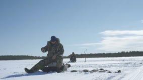El pescador coge un pescado, deporte de invierno, afición del invierno almacen de metraje de vídeo