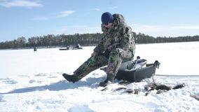 El pescador coge un pescado, deporte de invierno, afici?n del invierno almacen de video